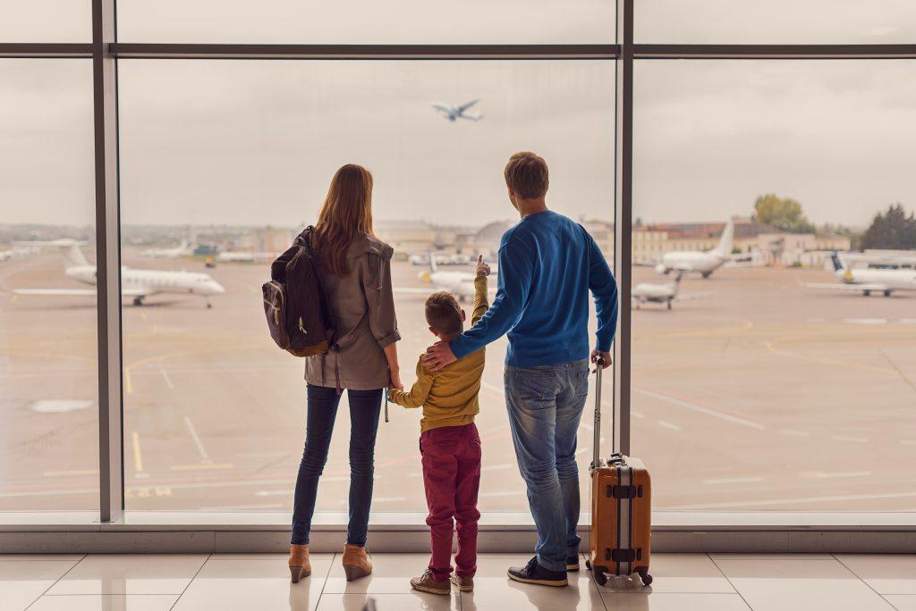En familj som ska flytta utomlands tittar ut genom fönstret på flygplats