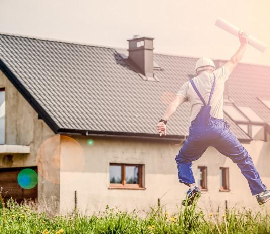 Remonttimies hyppää nurmikolla ilmaan. Hänellä on kädessään rakennuspiirustukset. Taustalla on keskeneräinen kivitalo.