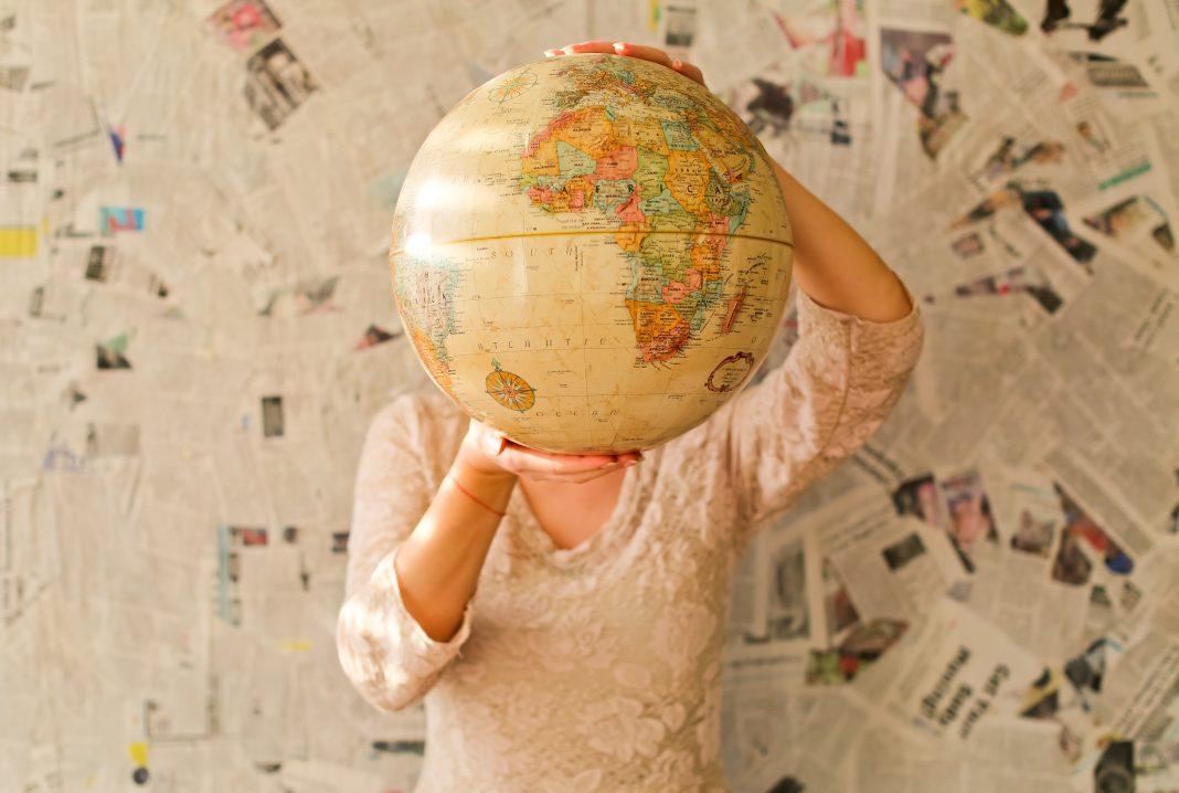 Tyttö pitää maapalloa kasvojen edessä