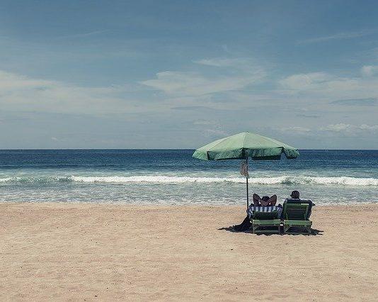 Pariskunta lepää paahteisella hiekkarannalla aurinkotuoleilla aurinkovarjon alla. Tautalla meri.