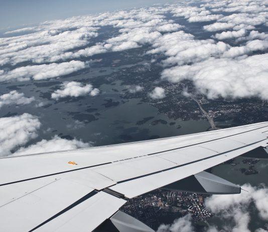 Kuva otettu lentokoneesta. Etualalla lentokoneen siipi, jonka ympärillä pilviä. Pilvien lomasta näkyy alhaalla kaupunki.äkyy suomalainen kaupunki.